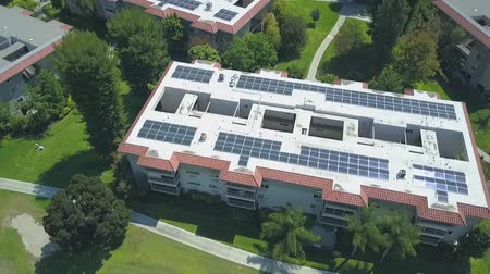 Aerial rising view above sunny rooftop apartment complex with solar panels generating clean energy