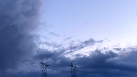 damp : Steel cable energy power pylon with time lapse slow storm clouds passing overhead