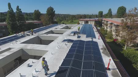 planlamacı : Aerial view over business complex solar panel in hard hat inspection on rooftop Stok Video