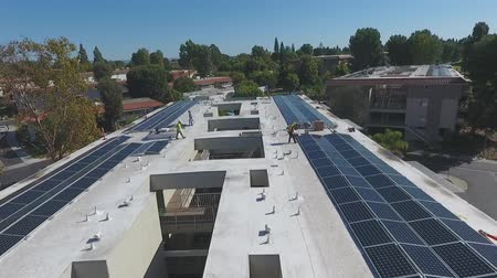 chapéu : Aerial over workers installing solar panels on rooftop of building complex