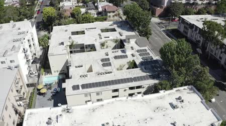 宿泊施設 : Aerial view orbiting urban real estate Los Angeles apartment complex rooftops in neighborhood