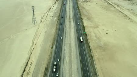 straight road : Aerial footage over trucks and cars on the fifteen freeway in the Mojave Desert Stock Footage