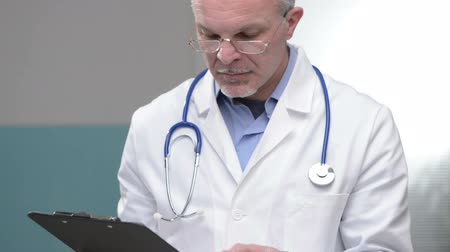 male : Senior confident doctor at hospital checking medical records. Stock Footage