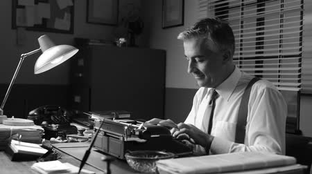 autor : Smiling vintage reporter working at office desk and typing on a typewriter.