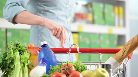 grocery : Woman walking fingers on shopping cart handle at supermarket.
