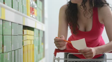 bevásárlókocsi : Young woman shopping with trolley at supermarket and checking a paper list.