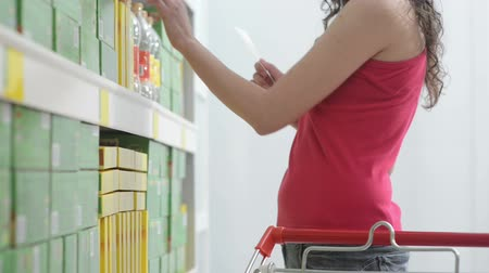 fresco : Woman at supermarket with shopping list taking products from the shelf.