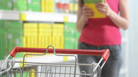 kordé : Young woman taking products from store shelves at supermarket with shopping cart on foreground.