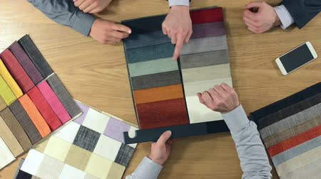 kumaş : Home decorator showing fabric swatches to his customers and touching the textiles textures hands top view Stok Video