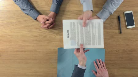 zawód : Confident candidate getting a job and shaking hands after a successful job interview hands top view unrecognizable people