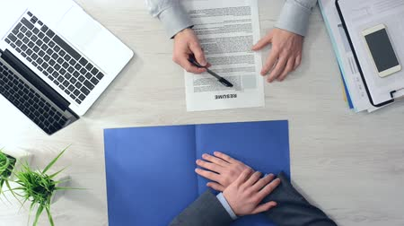 vágólapra : Businessman checking a candidates resume during a job interview and shaking hands after hiring him hands top view