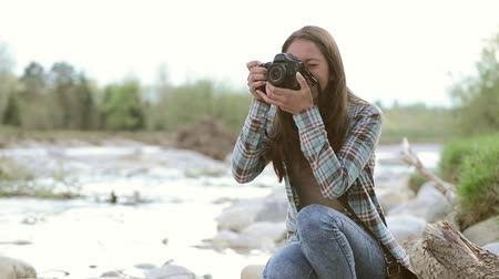 fotografando : Young smiling girl sitting along the river and taking pictures with her digital camera Vídeos