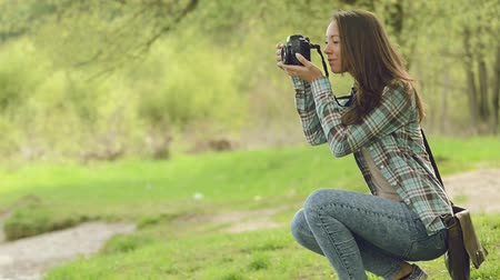 fotografando : Young beautiful girl at the park taking pictures with her camera, vegetation and people on background