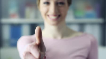 детеныш : Smiling cheerful woman giving a thumbs up and looking at camera, selective focus