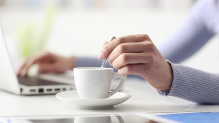 xícara de café : Young woman having a coffee break, she is stirring her espresso and using a laptop, hand close up, seamless loop