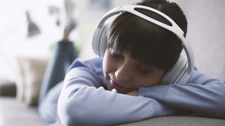 наслаждаться : Young woman lying on the sofa, wearing headphones and listening to music, home and entertainment concept Стоковые видеозаписи