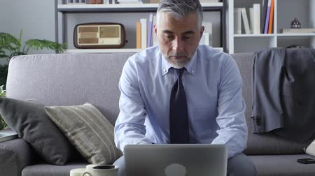 executivo : Efficient businessman at home sitting on the sofa and working with a laptop Vídeos