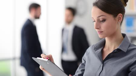 eficiente : Businesswoman checking a list on a clipboard and smiling at camera, office workers talking in the background Stock Footage