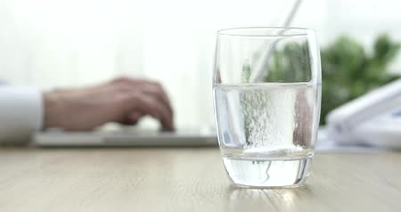 fizzing : Effervescent tablet falling into a glass of water and businessman working with a laptop on the background, healthcare concept Stock Footage