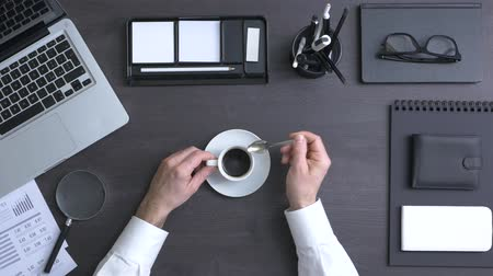 xícara de café : Businessman working at office desk and having a coffee break, top view