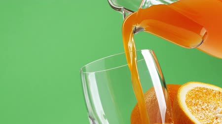 tápanyagok : Jug pouring fresh orange juice in a glass on green background, nutrition and diet concept