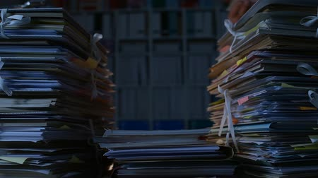 accumulating : Office clerk stacking paperwork and files on desk late at night, workload and bureaucracy concept