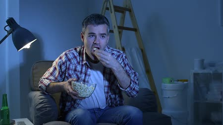 pipoca : He is cheering and eating popcorn. Smiling man relaxing at home at night