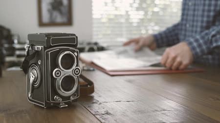 segregatory : Professional photographer working in his studio, he is watching film negatives in a binder, vintage twin lens reflex camera on the foreground Wideo