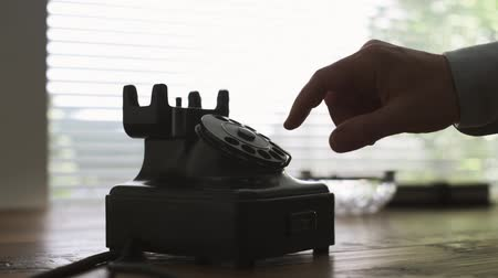 adresář : Man picking up the receiver and dialing a number on a vintage telephone dial on a desk, he is making a phone call, hands close up Dostupné videozáznamy