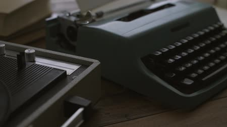 tonearm : Vintage desk with record player and typewriter: retro revival, relaxation and entertainment concept Stock Footage