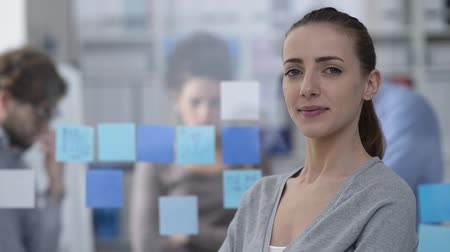 internar : Young smiling woman posing in the office and working on the background