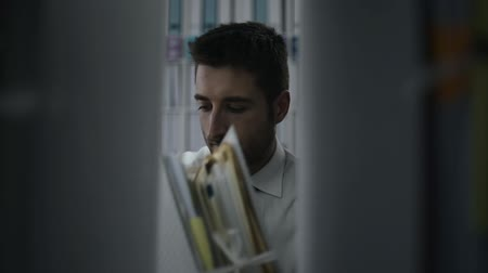 документация : Corporate office worker taking a folder with paperwork from a shelf