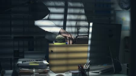 camionagem : Business employee packing his belongings in the office after being fired and turning off the light