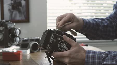 fotoğrafçı : Professional photographer working in his studio, he is cleaning a vintage twin lens reflex camera using a cloth, hobby and photography concept