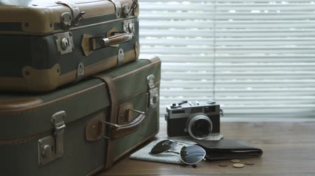 nostalgia : Ready packed vintage suitcases, room, map and wallet on a desktop: travel and tourism concept Stock Footage