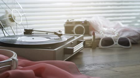 tonearm : Vintage record player with spinning record and womans accessories on a table, leisure and retro revival concept Stock Footage