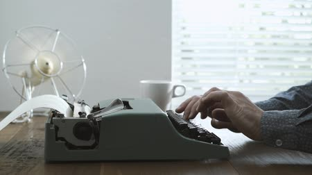 conta : Professional writer typing on a vintage typewriter next to a window, retro revival and creativity concept