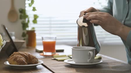 expressed : Woman having breakfast at home and pouring hot coffee in a cup using a moka pot Stock Footage
