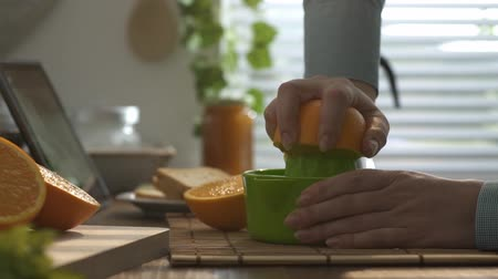 squeezer : Woman preparing a healthy fresh orange juice for morning breakfast in the kitchen, she is squeezing an orange with a manual juicer