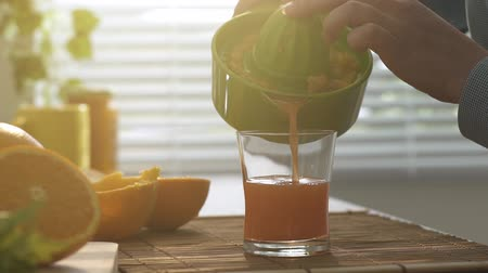 squeezer : Woman preparing a fresh orange juice for breakfast in the kitchen, she is pouring the juice in a glass