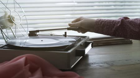tonearm : Woman playing music on a vintage record player, she is setting the tonearm on the turntable