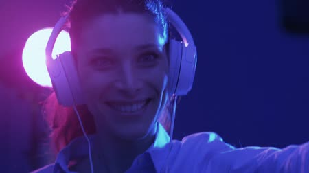 функция : Happy woman listening to music using headphones and videocalling, she is dancing at the disco and holding her smartphone