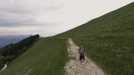 альпинизм : Young athletic man exploring mountains and running, drone aerial view