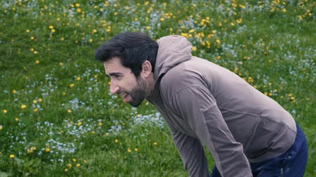 arquejo : Young jogger running outdoors in nature, he stops and checks his fitness tracker, sports and athletics concept