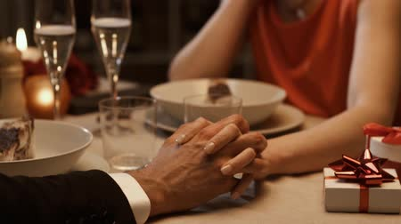 clasped : Romantic couple having a date at the restaurant and celebrating with gifts, they are joining their hands, relationships and feelings