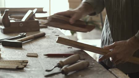 lumber : Carpenter working in his workshop, he is smoothing a wooden surface with sandpaper