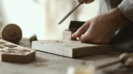 ustalık : Professional carpenter working in his workshop and carving wood using a gouge, woodworking and craftmanship concept Stok Video