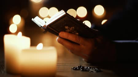 книгу : Man reading the Holy Bible and praying in the Church with lit candles, religion and faith concept