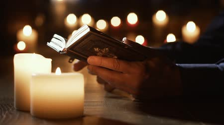 bible study : Man reading the Holy Bible and praying in the Church with lit candles, religion and faith concept