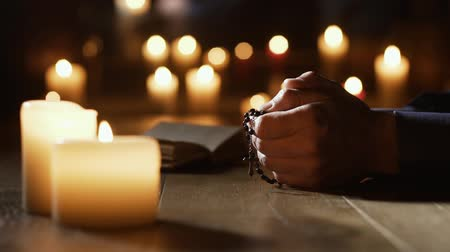 cristianity : Man praying the Holy Rosary in the Church and lit candles: religion and faith concept